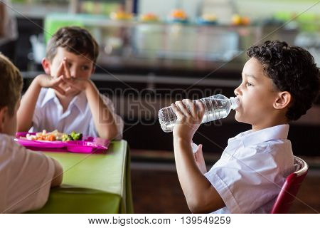 Schoolboy drinking water from bottle in canteen