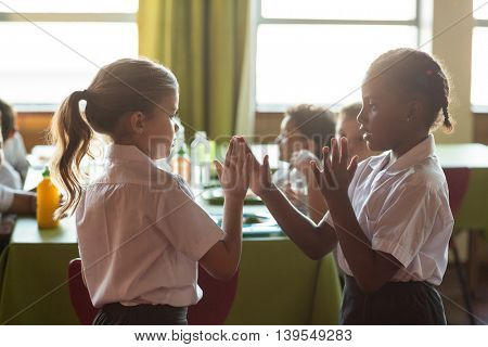 Schoolgirls playing clapping game in canteen