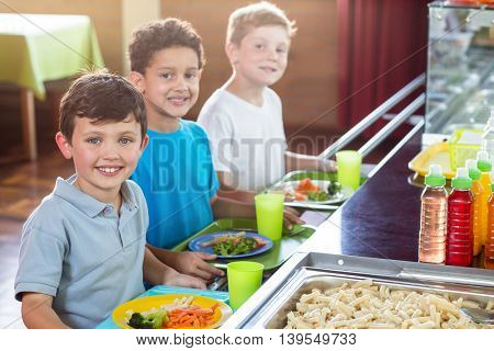 Portrait of smiling schoolboys standing near counter of school canteen