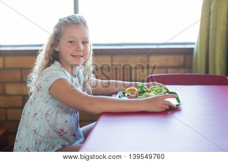 Portrait of cute girl having meal in canteen