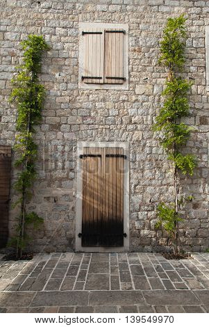 Wooden door in old town in Montenegro in house made of bricks with green plants.