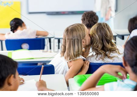 Rear view of girls gossiping in classroom