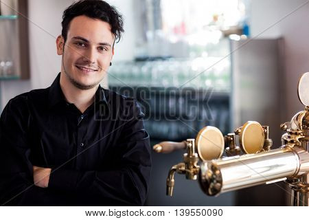 Portrait of young confident bartender standing at bar counter
