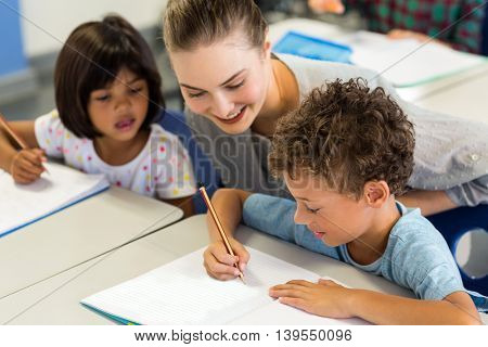Happy female teacher helping schoolchildren to write on book