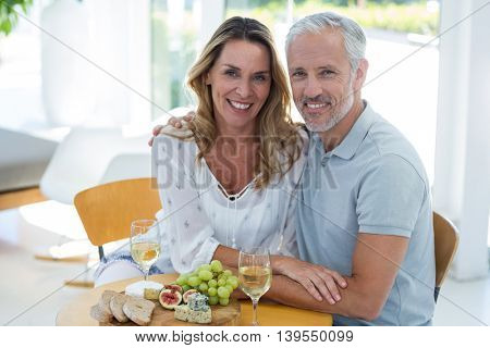 Portrait of happy mature couple by table in restaurant
