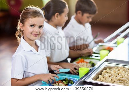 Portrait of smiling schoolgirl with classmate standing near canteen counter