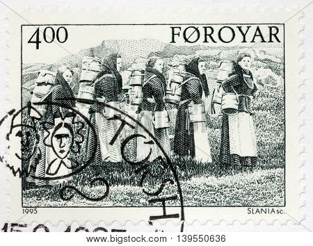 LUGA RUSSIA - JUNE 25 2016: A stamp printed by FAROE ISLANDS shows dairymaids carrying buckets circa 1995.