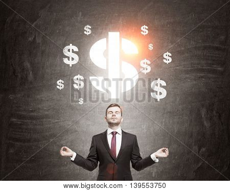 Businessman meditating in front of chalk board with dollar symbols sketch. Concept of thinking relaxation and future planning. Toned image