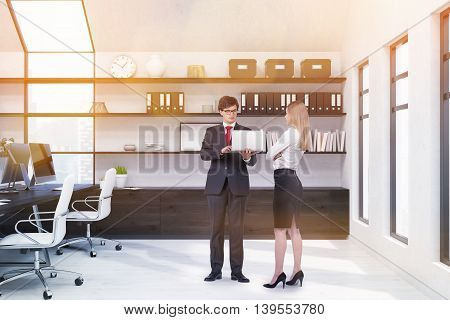 Pair of office people standing in room. Computers on desk. Shelf with boxes book clock and picture in background. Concept of brainstorming. 3d rendering. Mock up. Toned image