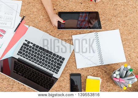 Young woman working with tablet computer. Her laptop notebook and office supplies on table. Concept of business and study work planning. Top view