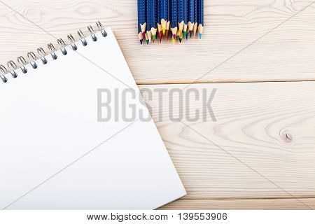 Set of pencils lie above empty notebook on wooden table. Concept of creativity and different possibilities. Top view. Mock up