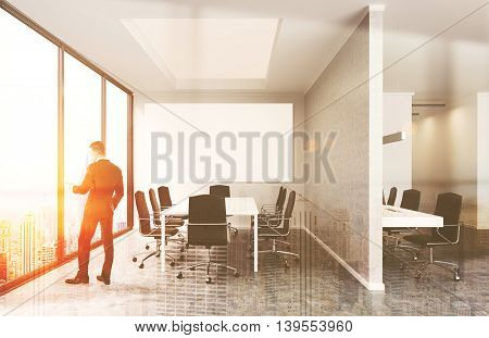 Young businessman standing near office window looking at New York. Large white table surrounded by armchairs. Big whiteboard on wall. 3d rendering. Mock up. Toned image. Double exposure.