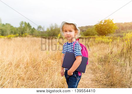 A Little Girl With A Backpack And A Book