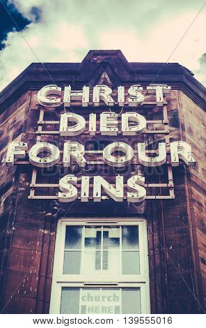 A Neon Sign On An Old Building Saying Christ Died For Our Sins