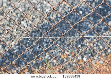 close up rusty barbed wire fence with stone background