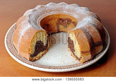 Homemade marble cake with cocoa sprinkled with sugar on a wooden table