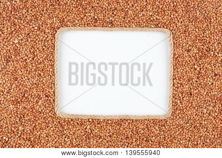 Frame made of rope with buckwheat grains and a white background with space for your text