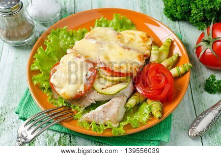 Oven-roasted fish fillet with courgettes and tomatoes under a cheese crust