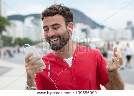 Happy man with red shirt and cellphone in the city listening music