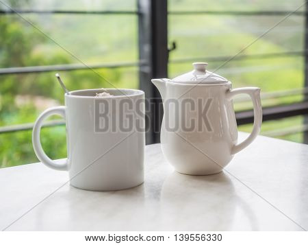 White Teapot And Tea Cup On The Table At Boh Tea Plantation