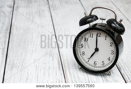 Black alarm clock on a old white wooden background