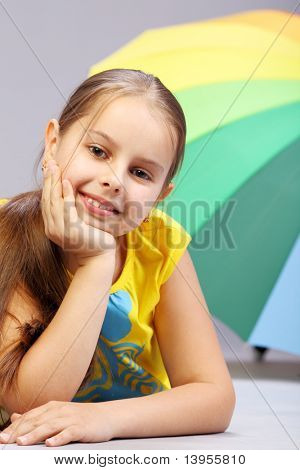 Young smiling girl with multicolor umbrella