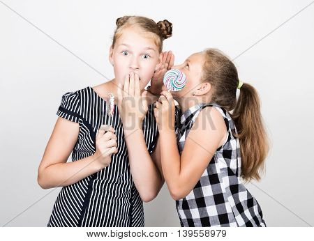 Two cute little girlfriend eating bright lollipops. Funny kids. Best friends pamper and posing. one of them whispers secret in the ear.