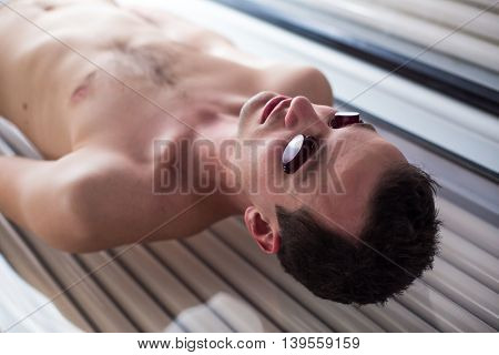 Handsome young man relaxing during a tanning session in a modern solarium, taking care of himself, enjoying the artificial sunlight.