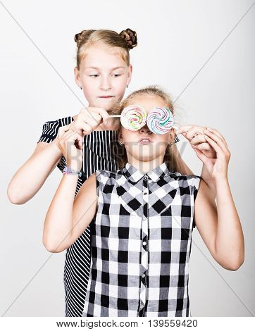 Two cute little girlfriend eating bright lollipops. Funny kids. Best friends pamper and posing.