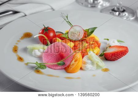 Fruit Tartare With Slices Of Salmon, Red Caviar And Tomato On A White Plate