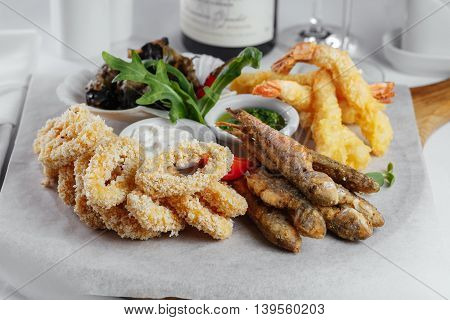 Fried Fish With Sauce And Greens With Squid Rings, Mussels And Shrimp On A White Paper