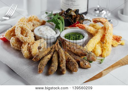 Squid Rings In Batter, Fish, Mussels And Shrimp On A Wooden Tray