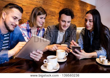 Happy friends using digital tablet and mobile phone while sitting at restaurant