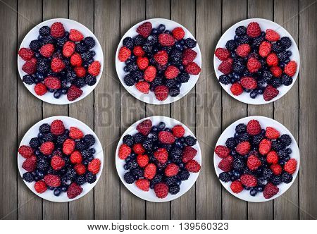 Various berries in a plate on a wooden table. Top view. Treats for guests. In anticipation of the arrival of friends. Red and blue raspberry and blueberry. Summer.