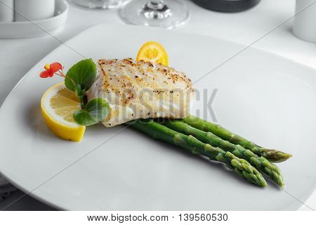 Fish With Lemon And Asparagus On A White Plate