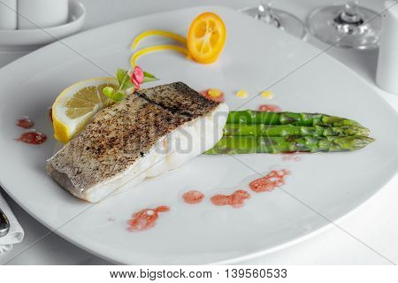 Baked Fish With Asparagus And Lemon On A White Plate