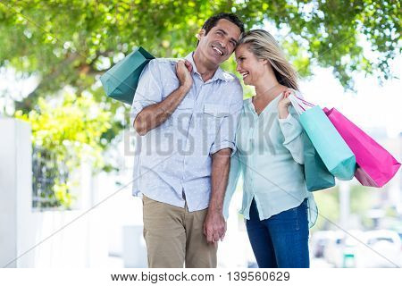 Cheerful couple with shopping bags standing on street in city