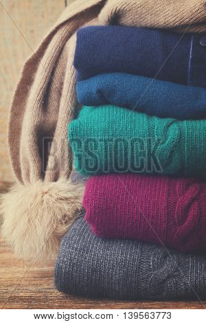 stack of folded woolen gray, green, blue and red clothes close up, retro toned