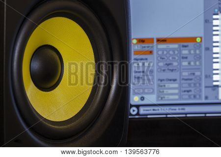 Close up shot of an audio speaker, with music production software in the background