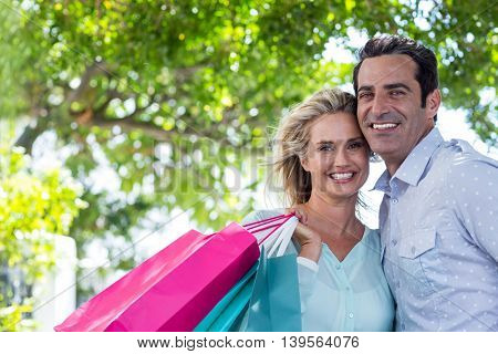 Portrait of happy couple with shopping bags against trees in city