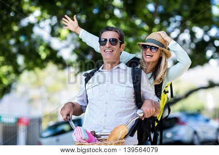 Cheerful couple riding bicycle on street in city