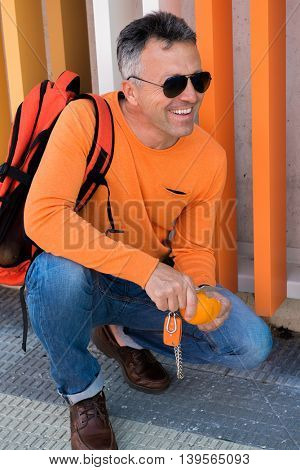 Male outdoor portrait. Man standing near colored building with orange, keychain, car keys knife.