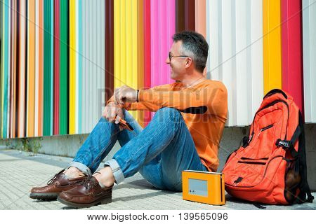 Street fashion. Male outdoor portrait. Man sitting near colored urban wall in jeans, orange sweater with backpack and smart phone.