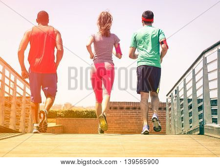 Friends jogging at city park view from back - Multiracial group of runners training outdoor rear scene - Nostalgic concept of healthy lifestyle and leisure activity together