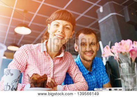 young man and woman with laptop typing on the keyboard in cafe. palm, tablet PC and laptop closeup