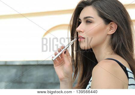 Beautiful Woman Smokes An Electronic Cigarette Outdoors