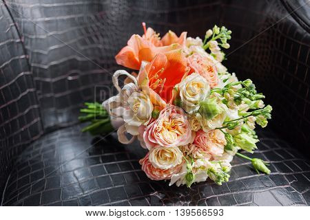Wedding bouquet on leather chair. Bride's traditional symbolic accessory. Floral composition with peach colored roses.