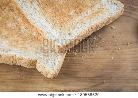 Close focus on edge of brown whole wheat toast on wood background with small crumb.