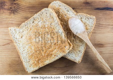 Top view on two brown whole wheat toast with sweet white jam on wooden teaspoon putting on wood background.