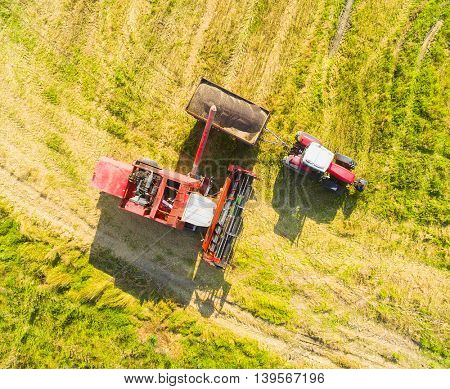 Aerial view of combine harvester and tractor. Harvest of rapeseed field. Industrial background on agricultural theme. Biofuel from Czech countryside. Agriculture and environment in European Union.